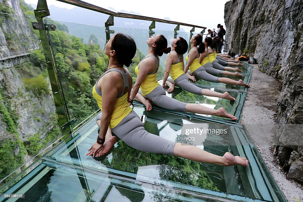 More than ten yoga enthusiasts perform yoga on a 236-meter-long glass plank road on May 24, 2016 in Yichang, Hubei Province of China. The glass plank road along a 7,500-meter-long cliff plank road is attractive in Yichang City.