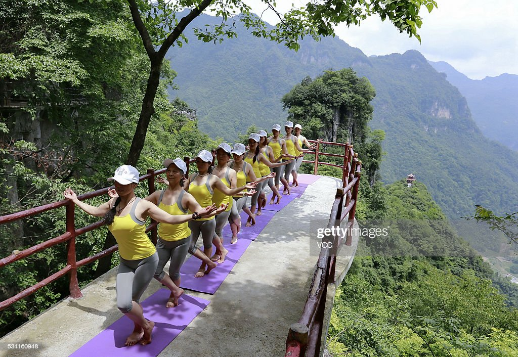 More than ten yoga enthusiasts perform yoga on a cliff plank road on May 24, 2016 in Yichang, Hubei Province of China. The glass plank road along a 7,500-meter-long cliff plank road is attractive in Yichang City.
