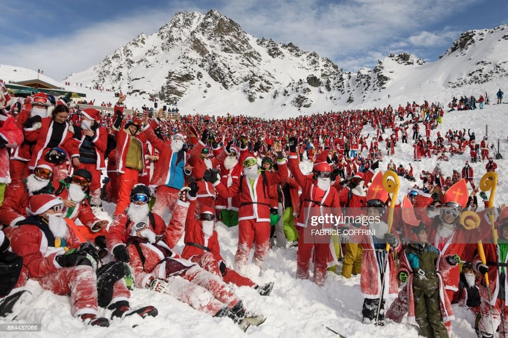 TOPSHOT - More that 2,000 people disguised as Santa Claus pose for a picture at the ski resort of Verbier, Swiss Alps, on December 2, 2017. The ski resort offered a daily pass to every skier wearing Santa dress to celebrates the ski season's opening day. / AFP PHOTO / Fabrice COFFRINI