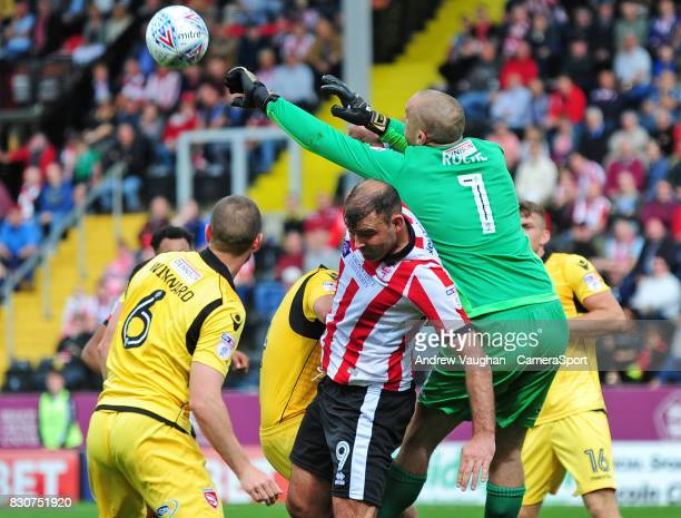 Morecambe's Barry Roche gets above Lincoln City's Matt Rhead to punch clear during the Sky Bet League Two match between Lincoln City and Morecambe at...