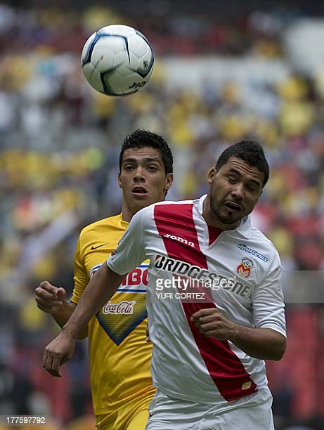 Morelia's Jose Olvera disputes the ball with America's forward Raul Jimenez during their Apertura 2013 Mexican league football match on August 24...