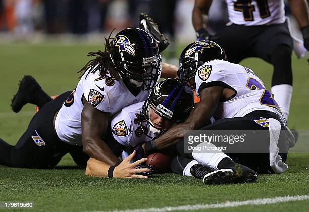 Morgan Cox, Chykie Brown, and Josh Bynes of the Baltimore Ravens recover a fumble by Wes Welker of the Denver Broncos following a punt in the second...