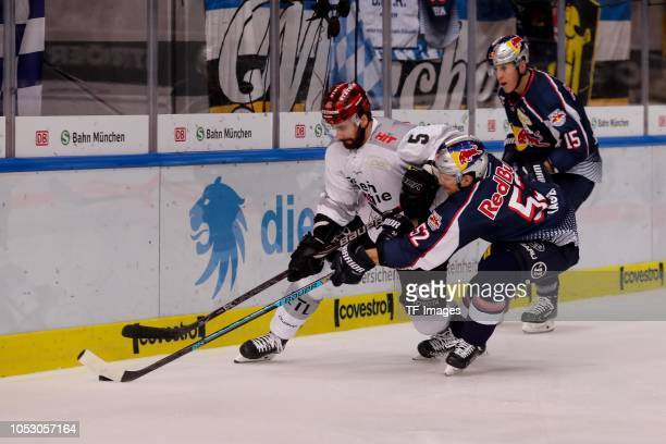 Morgan Ellis of Koelner Haie and Patrick Hager of Red Bull Muenchen battle for the ball during the German Ice Hockey match between EHC Red Bull...