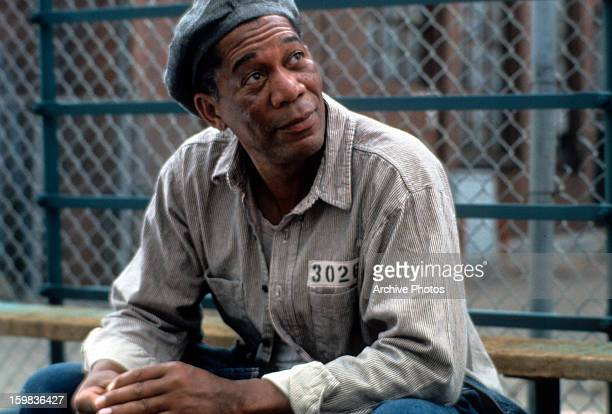 Morgan Freeman sitting outside with a hat and prison uniform on in a scene from the film 'The Shawshank Redemption' 1994