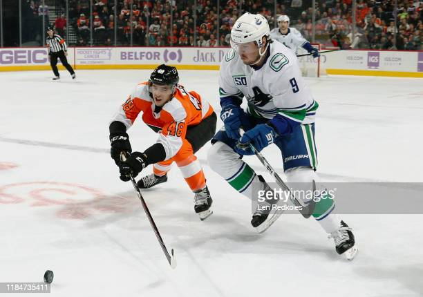 Morgan Frost of the Philadelphia Flyers and JT Miller of the Vancouver Canucks battle for control of the loose puck on November 25 2019 at the Wells...