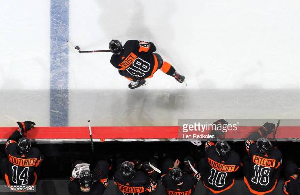Morgan Frost of the Philadelphia Flyers skates the puck along his bench against the New York Rangers on December 23 2019 at the Wells Fargo Center in...