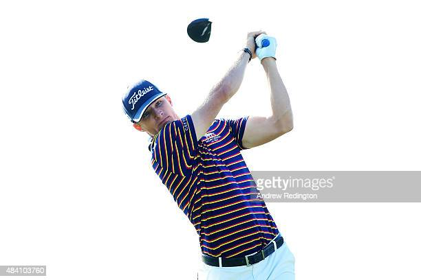 Morgan Hoffmann of the United States watches his tee shot on the ninth hole during the continuation of the weather-delayed second round of the 2015...