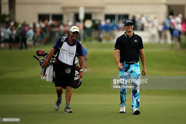Morgan Hoffmann talks with his caddie Steve Underwood as they walk down the fairway of the first hole during the third round of the World Golf...