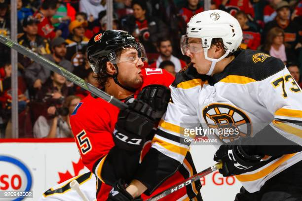 Morgan Klimchuk of the Calgary Flames and Charlie McAvoy of the Boston Bruins battle for position in an NHL game on February 19 2018 at the...