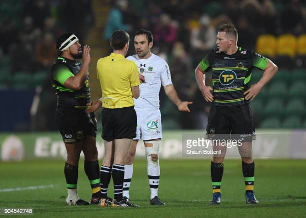 Morgan Parra of Clermont Auvergne and Dylan Hartley of Northampton Saints talk with referee George Clancy as Campese Ma'afu looks on during the...