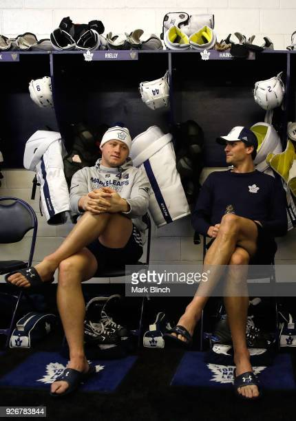 Morgan Rielly and Ron Hainsey of the Toronto Maple Leafs sit in their locker room stalls prior to the Coors Light NHL Stadium Series game at United...