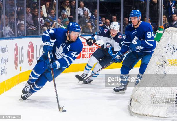Morgan Rielly and Tyson Barrie of the Toronto Maple Leafs skates against Patrik Laine of the Winnipeg Jets during the second period at the Scotiabank...