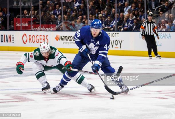 Morgan Rielly of the Toronto Maple Leafs plays the puck against Luke Kunin of the Minnesota Wild during the first period at the Scotiabank Arena on...