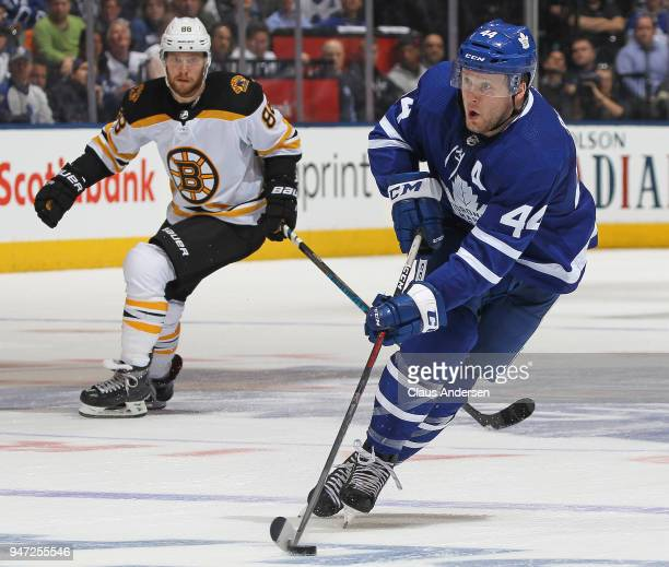 Morgan Rielly of the Toronto Maple Leafs skates with the puck ahead of David Pastrnak of the Boston Bruins in Game Three of the Eastern Conference...
