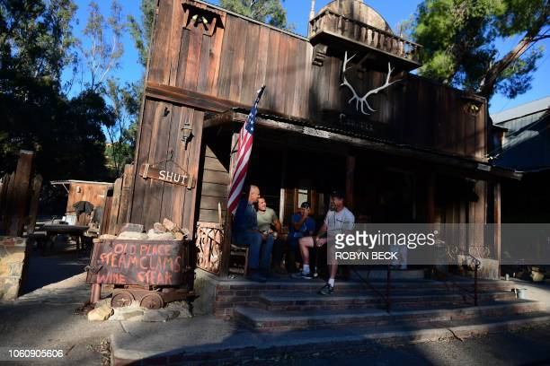 Morgan Runyon sits with a friend on the porch of his restaurant The Old Place after ignoring evacuation orders to stay behind and save the restaurant...