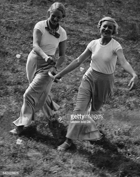Morgentraining - zwei junge Frauen laufen auf einer Wiese und halten einen Ring fest veröffentlicht: Dame 19/1933 Foto: Martin Munkacsy