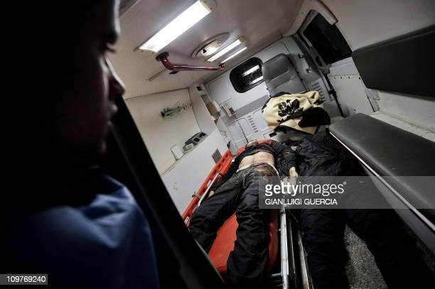 A morgue worker of the Ajdabiya hospital looks at bodies of two Libyan rebel fighters allegedly killed during fierce clashes between Libyan regime...
