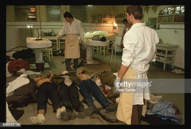 Morgue workers at the Bucharest Emergency Hospital stand over the bodies of men killed in street fighting in Bucharest during the revolution of...