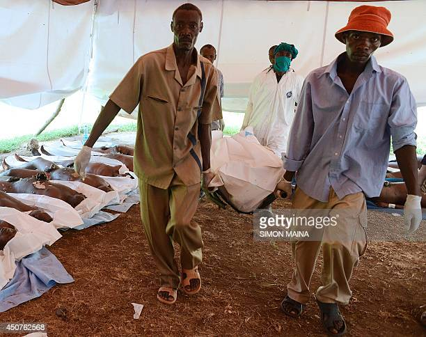 Morgue workers helped by relatives carry a body ready burial at the Mpeketoni hospital in Lamu county along the Kenyan coast on June 17 after some 50...