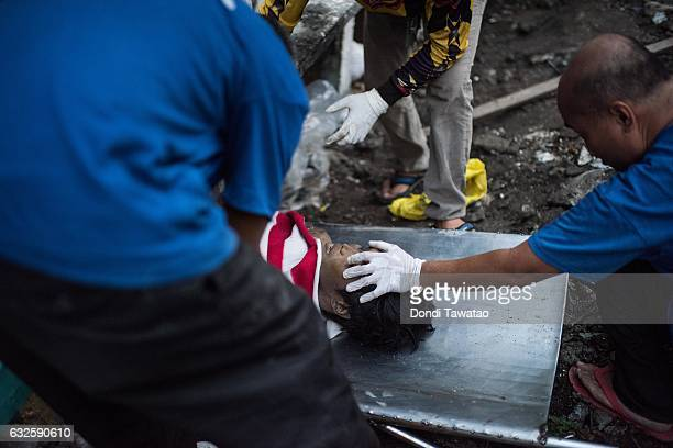 Morgue workers shove unclaimed bodies inside a tomb on January 24 2017 in Manila Philippines Many bodies of victims of extrajudicial killings lay...