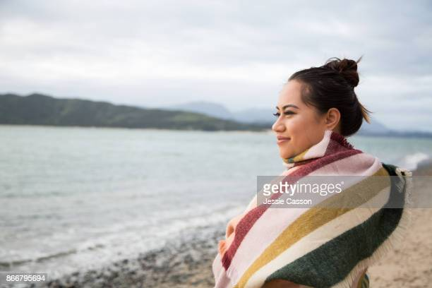 Māori woman wrapped in a shawl looks out to sea on a beautiful beach