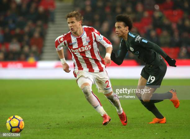 Moritz Bauer of Stoke City and Leroy Sane of Manchester City chase the ball during the Premier League match between Stoke City and Manchester City at...