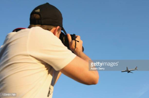 Moritz Koester photographs an airplane taking off from Berlin Tegel Otto Lilienthal Airport on September 3 2011 in Berlin Germany The airport which...