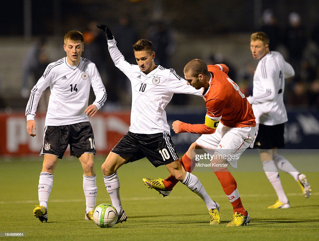 Moritz Leitner of Germany (L) challenges Pajtim Kasami of Switzerland during the international friendly match between U20 Switzerland and U20 Germany at Eps Stadium on March 26, 2013 in Baden, Switzerland. Robin Knoche (14) and Tobias Schilk of Germany watching scene.