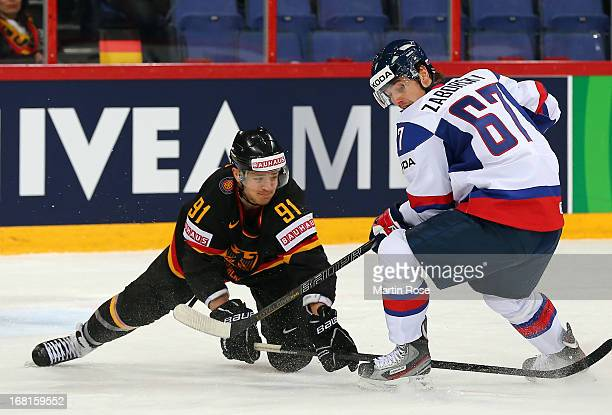 Moritz Mueller of Germany and Tomas Zaborsky of Slovakia battle for the puck during the IIHF World Championship group H match between Germany and...