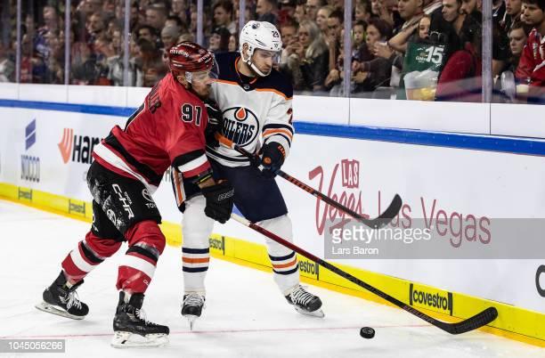 Moritz Mueller of Haie challenges Leon Draisaitl of Edmonton during the NHL Global Series Challenge game between Edmonton Oilers and Kolner Haie at...