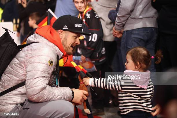 Moritz Mueller of the German ice hockey team is welcomed by his daughter during the welcome ceremony for the members of Team Germany after their...