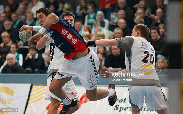 Moritz Schapsmeier and Einar Orn Jonsson of Minden challenges Blazenko Lackovic of Flensburg during the Bundesliga game between GWD Minden and SG...