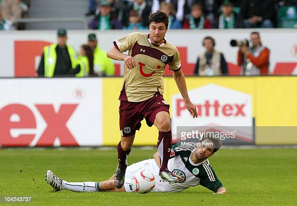 Moritz Stoppelkamp of Hannover battles for the ball with Diego Ribas da Cunha of Wolfsburg during the Bundesliga match between VFL Wolfsburg and...