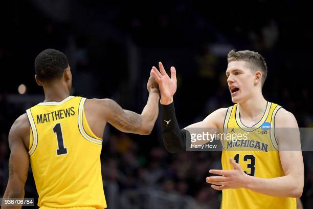 Moritz Wagner and Charles Matthews of the Michigan Wolverines celebrate in the second half while taking on the Texas AM Aggies in the 2018 NCAA Men's...