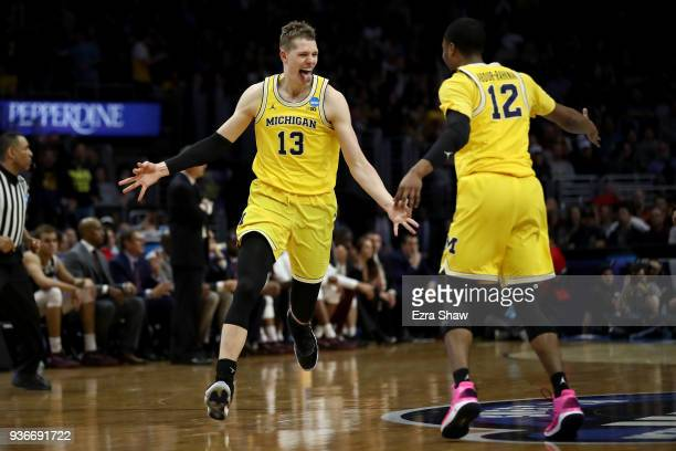 Moritz Wagner celebrates with Muhammad-Ali Abdur-Rahkman of the Michigan Wolverines after Wagner makes a three-pointer in the first half against the...