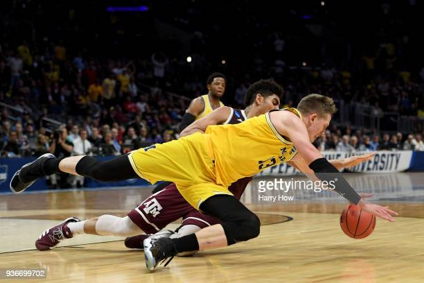 Moritz Wagner of the Michigan Wolverines and Tyler Davis of the Texas AM Aggies battle for a loose ball in the first half in the 2018 NCAA Men's...