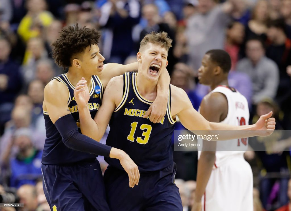 Moritz Wagner #13 of the Michigan Wolverines celebrates a shot with D.J. Wilson #5 in the second half against the Louisville Cardinals during the second round of the 2017 NCAA Men's Basketball Tournament at the Bankers Life Fieldhouse on March 19, 2017 in Indianapolis, Indiana. Michigan Wolverines won 73-69.