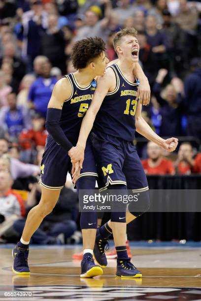 Moritz Wagner of the Michigan Wolverines celebrates a shot with D.J. Wilson in the second half against the Louisville Cardinals during the second...