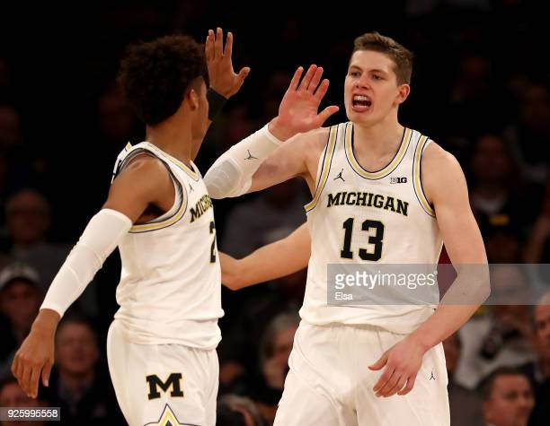 Moritz Wagner of the Michigan Wolverines celebrates his basket with teammate Jordan Poole in the first half against the Iowa Hawkeyes during the...