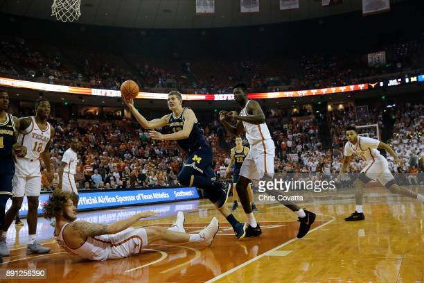 Moritz Wagner of the Michigan Wolverines commits a charge against Dylan Osetkowski of the Texas Longhorns at the Frank Erwin Center on December 12...