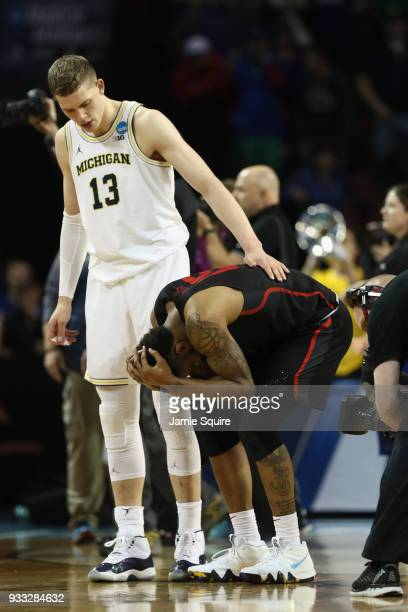 Moritz Wagner of the Michigan Wolverines consoles Devin Davis of the Houston Cougars who reacts to their 63-64 loss to the Michigan Wolverines in the...