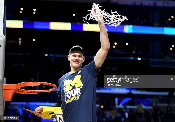 Moritz Wagner of the Michigan Wolverines cuts down the net after the Wolverines 5854 victory against the Florida State Seminoles in the 2018 NCAA...