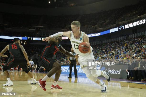 Moritz Wagner of the Michigan Wolverines drives against Wes VanBeck of the Houston Cougars in the second half during the second round of the 2018...