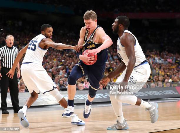 Moritz Wagner of the Michigan Wolverines drives with the ball against Mikal Bridges and Eric Paschall of the Villanova Wildcats in the first half...