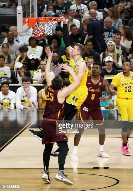 Moritz Wagner of the Michigan Wolverines dunks in the second half against Cameron Krutwig of the Loyola Ramblers during the 2018 NCAA Men's Final...