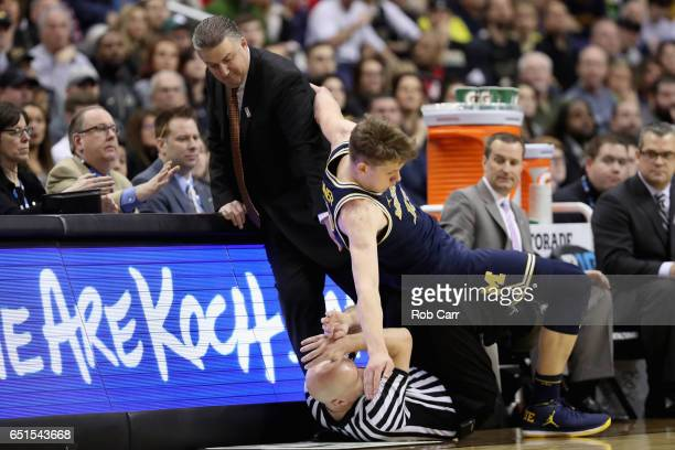 Moritz Wagner of the Michigan Wolverines falls onto head coach Matt Painter of the Purdue Boilermakers and official DJ Carstensen during the Big Ten...