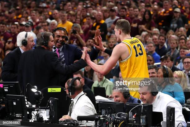 Moritz Wagner of the Michigan Wolverines high fives TV personalities Jim Nantz, Bill Raftery and Grant Hill after jumping off the court in the second...