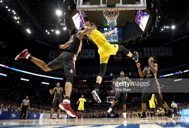 Moritz Wagner of the Michigan Wolverines is fouled by CJ Walker of the Florida State Seminoles in the first half in the 2018 NCAA Men's Basketball...