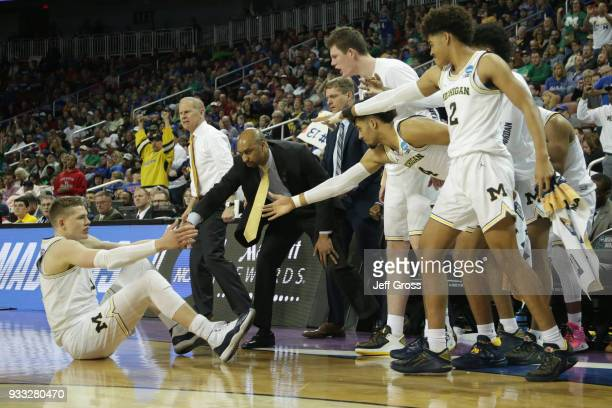 Moritz Wagner of the Michigan Wolverines makes a basket as he is fouled and knocked to the floor to be helped up by teammates as they take on the...