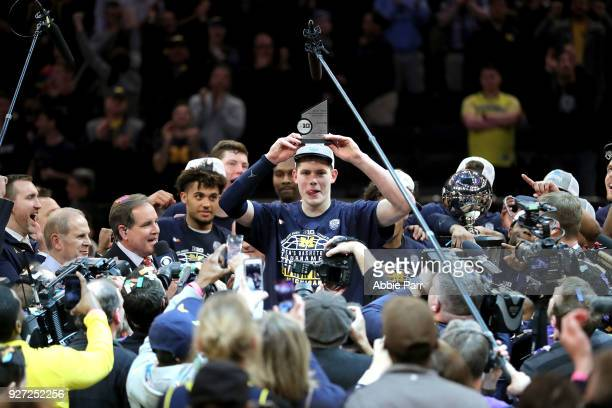 Moritz Wagner of the Michigan Wolverines raises his MVP trophy after defeating the Purdue Boilermakers 7566 during the championship game of the Big...